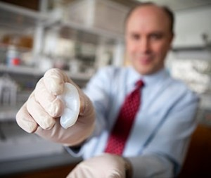 Lawrence Bonassar holds an artificial ear made with 3D printing and injectable molds. (Lindsay France, Cornell University)